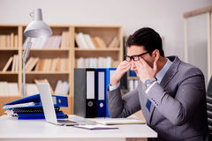 The sleepy businessman working in office Stock Photo