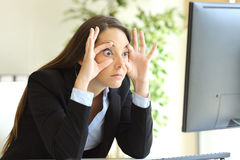 Sleepy businesswoman trying to keep eyes opened stock images