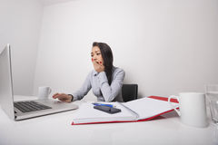 Sleepy businesswoman working on laptop at office desk Stock Photo