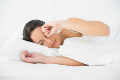 Sleepy casual brunette waking up and rubbing her eyes Stock Photo