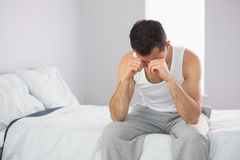 Sleepy casual man sitting on bed rubbing his eyes Royalty Free Stock Images