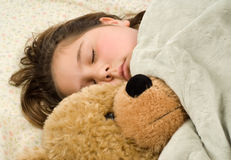Sleepy Child. Young girl snuggling with a stuffed bear, covered in a warm blanket royalty free stock photography
