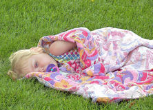 Sleepy child in grass with pacifier. Little blond girl napping with pacifier and wrapped in terry cloth towel in grass stock photography