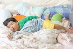 A sleepy child is sleeping on the comfortable bed. In the morning, his parent can not wake him up royalty free stock photos