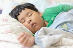 A sleepy child is sleeping on the comfortable bed. In the morning, his parent can not wake him up stock images