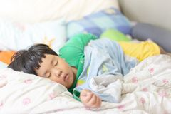 A sleepy child is sleeping on the comfortable bed. In the morning, his parent can not wake him up stock image