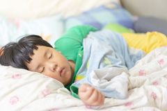 A sleepy child is sleeping on the comfortable bed. In the morning, his parent can not wake him up stock photo
