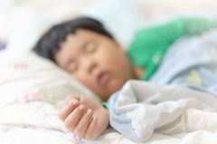A sleepy child is sleeping on the comfortable bed. In the morning, his parent can not wake him up royalty free stock images