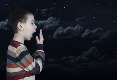 Sleepy child that yawning. Night starry sky stock photo