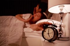 Sleepy couple in bed with extending hand to alarm clock in the m Royalty Free Stock Images