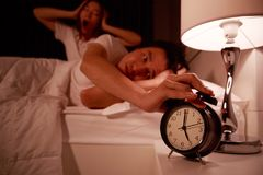 Sleepy couple in bed with extending hand to alarm clock in the m Royalty Free Stock Photos