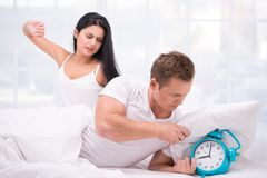 Sleepy couple waking up by an alarm clock ringing Royalty Free Stock Images