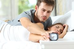 Sleepy couple waking up turning off alarm clock in the bed royalty free stock images