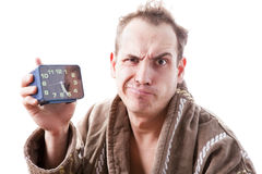 Sleepy disgruntled man with alarm clock in hand early in the mor Stock Photo