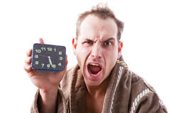 Sleepy disgruntled man with alarm clock in hand early in the mor Royalty Free Stock Photography