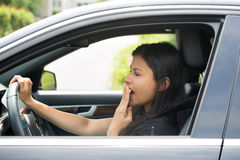 Sleepy driver. Closeup portrait tired young attractive woman with short attention span, driving her car after long hours trip, yawning at wheel, isolated outside Royalty Free Stock Image