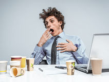 Sleepy exhausted or bored young businessman in yawn. Stock Images