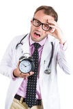 Sleepy, exhausted male doctor wearing glasses holding an alarm clock, tired after a busy da Stock Image