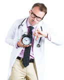 Sleepy, exhausted male doctor wearing glasses holding an alarm clock, tired after a busy day, Stock Photography