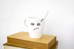 Sleepy face coffee cup on text books Stock Photography