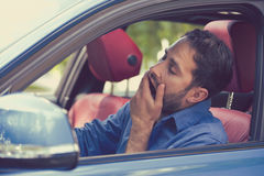 Sleepy fatigued yawning exhausted young man driving his car. In traffic after long hour drive. Transportation sleep deprivation accident concept royalty free stock image