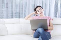 Sleepy female model with laptop Stock Photography