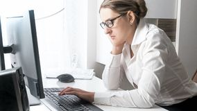 Sleepy female office worker sitting at big window. Sleepy female office worker sitting at window Royalty Free Stock Photography