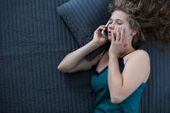Sleepy female talking on phone Stock Images