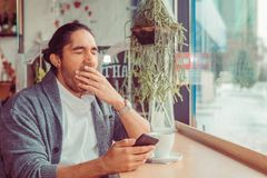 Sleepy funny man, hand on mouth yawning looking at smart phone being bored by phone conversation, texting royalty free stock photo