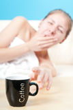 Sleepy girl. Laying in bed looking for the coffee on blue background Stock Photography