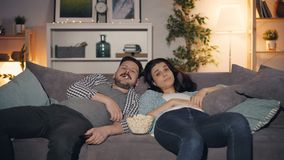 Sleepy girl and guy watching TV and eating popcorn at night in apartment stock footage