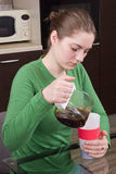 Sleepy girl pouring coffee in cup Stock Photo