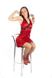 Sleepy girl in red dress sitting on the chair royalty free stock photos