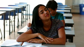 Sleepy girl relaxing on desk while studying in classroom. At school stock video footage