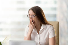 Sleepy girl struggles with drowsiness at work. Businesswoman yawning while sitting in office. Woman feeling lack of sleep during working day. Female employee Stock Photos