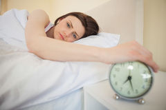 Sleepy girl turning off her alarm clock Royalty Free Stock Photo