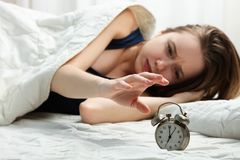 Sleepy girl wakes up and turns off alarm clock stock images