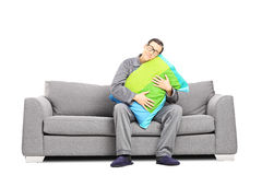 Sleepy guy in pajamas, sitting on sofa embracing a pillow Stock Image