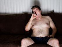 Sleepy guy sitting on the couch Royalty Free Stock Photo