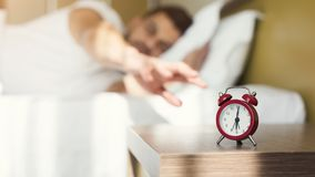 Sleepy guy waking up early after alarm clock signal. Sleepy guy waking up early after hearing alarm clock signal on monday morning, reaching button on the clock stock images