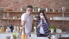 Sleepy or hangover man and woman in the morning drinking coffee in the kitchen stock video footage