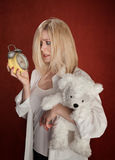 Sleepy Head. Pretty blond woman with bear and clock wakes up late stock image
