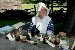 Sleepy Hollow, NY: 18th Century Interpreter Guide. Woman interpreter wearing 18th century garb with traditional colonial medicines and herbal potions at historic Stock Photo