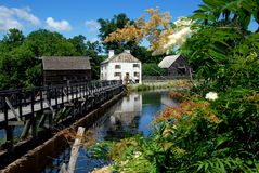 Sleepy Hollow, NY: Philipse Manor. Wooden mill pond bridge, grist mill, white manor house, and old Dutch barn at historic c. 1750 Philipsburg Manor built by Royalty Free Stock Image