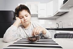 Sleepy kid eating cereal bites closeup. Sleepy kid in pajama eating cereal bites at the kitchen closeup stock photos