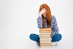 Sleepy lady leaning on stack of books and having headache Royalty Free Stock Image