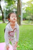Sleepy little Asian kid girl in green grass lawn. Closed eyes child outdoor.  royalty free stock image