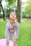 Sleepy little Asian kid girl in green grass lawn. Closed eyes child outdoor.  stock images