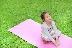 Sleepy little Asian kid girl sitting on pink mattress in green grass lawn. Closed eyes child outdoor.  royalty free stock photos