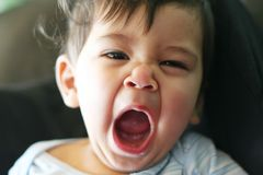 Sleepy Little Babe. Sleepy little baby boy yawning while sitting on the couch Stock Photography